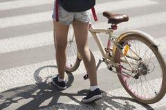 Kid with bike walking on pedestrian crossing stock images