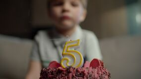Close up of kid blowing out candle with number 5 on chocolate birthday cake in slow motion. Five years old boy