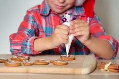 Close up of kid decorating the gingerbread cookies Stock Images