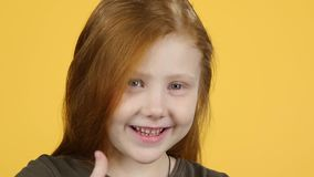 Close-up kid girl gesturing two finger-up signs to show like, slow motion. Close-up sweety kid girl gesturing two finger-up signs to show like on the yellow stock footage