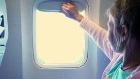 Close-up. Kid girl raises the porthole curtain in the airplane`s cabin, from there shines a bright light. girl looking