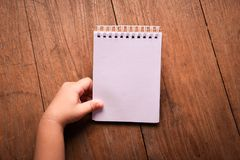 Close up kid hand holding Notebook paper  on table wood background. Stock Photo
