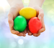 Close up of kid hands holding colored eggs Stock Photos