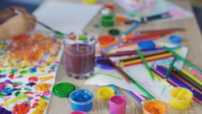 Close-up of kid's hand painting a picture at preschool art club, creativity. Stock footage stock footage