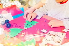 Kid attaches stickers on paper Christmas tree stock photos