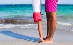 Close up kid's and male feet at the white sandy Stock Images