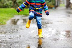 Close-up of kid wearing yellow rain boots and walking during sleet, rain and snow on cold day. Child in colorful fashion casual clothes jumping in a puddle Stock Image