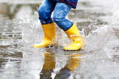 Close-up of kid wearing yellow rain boots and walking during sleet, rain and snow on cold day. Child in colorful fashion casual clothes jumping in a puddle Royalty Free Stock Images