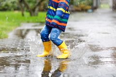 Close-up of kid wearing yellow rain boots and walking during sleet, rain and snow on cold day. Child in colorful fashion. Casual clothes jumping in a puddle royalty free stock images