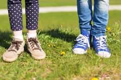 Close up of kids legs in shoes on grass outdoors Royalty Free Stock Photo