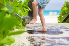 Close up of kids legs under a beach shower Stock Photography