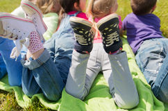 Close up of kids lying on picnic blanket outdoors. Summer, childhood, leisure and people concept - close up of happy kids lying on picnic blanket outdoors Stock Photos