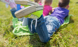 Close up of kids lying on picnic blanket outdoors. Summer, childhood, leisure and people concept - close up of happy kids lying on picnic blanket outdoors Royalty Free Stock Image