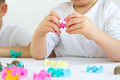 Close-up of kids playing board game while sitting at the table at home, suction cup construction sets for child development stock photo