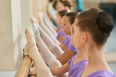 Close up kids stretching on ballet barre. Group of young ballerinas with legs on ballet barre in dance class. School of classical ballet dance Royalty Free Stock Photography
