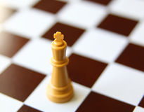Close-up of a king chess piece. On a checker board Stock Image