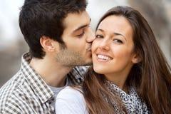 Close up kiss on girls cheek. Close up portrait of boy kissing girlfriend on cheek outdoors Stock Photo