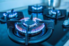 Close-up kitchen stove cook with blue flames burning.  royalty free stock photos