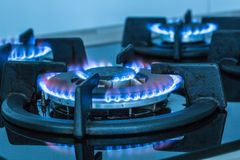 Close-up kitchen stove cook with blue flames burning.  stock image