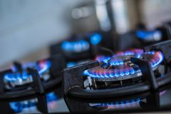 Close-up kitchen stove cook with blue flames burning.  royalty free stock photography