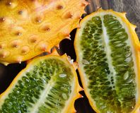 Close up of kiwano fruits. Close up view of a whole and halved kiwano t on a wooden cutting board, lit with natural sunlight stock photography