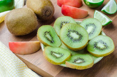 Close up kiwi fruit slice on dish with wooden board background Royalty Free Stock Photography
