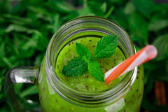 Close-up of a kiwi juice. Top view of a mason jar of green smoothie on a leaves background. Health and nature concept. Royalty Free Stock Images