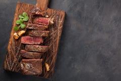 Close-up klaar om het rundvleesrassen van lapje vleesnew york van zwarte Angus met kruiden, knoflook en boter op een houten Raad  Stock Afbeelding