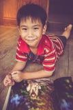 Close-up knappe Aziatische jongen die en beeldalbum glimlachen lezen ED Royalty-vrije Stock Afbeeldingen