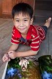 Close-up knappe Aziatische jongen die en beeldalbum glimlachen lezen ED Stock Foto's