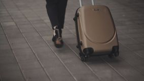 Business lady going to taxi parking from the airport with her luggage. Girl in heels stepping and roll suitcase on. Close up, Knee or ground level shot: Business stock video footage