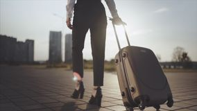 Business lady going to taxi parking from the airport with her luggage. Girl in heels stepping and roll suitcase on. Close up, Knee or ground level shot stock video footage