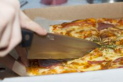 Close-up of a knife cutting pizza. royalty free stock image