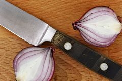 Close up knife with two slices of red onion on cutting board Royalty Free Stock Images