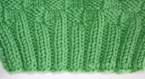 Close up of the knitted Rib Stitch.  Knit two, purl two, knit two, purl two in a pretty green color wool.  Then knitted in a Baske Stock Images
