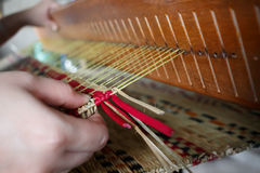 Close up of knot mat with woman hand on woven mat Royalty Free Stock Images