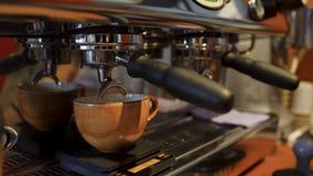 Close-up in kop van koffie die van koffiemachine wordt gegoten Art Coffevoorbereiding met beroepsuitrusting in koffiewinkel stock foto