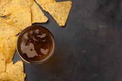 Close-up koud bier in een lang glas en van graan Nacho op een donkere steen met exemplaarruimte Hoogste mening stock fotografie