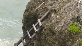 Close up of ladder used to access a rock. Close up of a wooden ladder from the shore, used to access the top of a large rock in the ocean stock footage