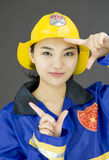 Close up of a lady firefighter framing her face with finger frame Royalty Free Stock Image