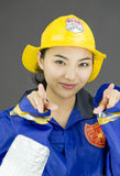 Close up of a lady firefighter pointing with both hands Royalty Free Stock Image