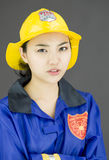 Close up of a lady firefighter wearing yellow helmet and blue fire protection suit Stock Photography