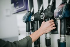 Girl holding petrol hose in arm outdoor. Close up lady hand taking the petrol pump nozzle while locating at station royalty free stock photo