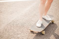 Close up of lady leg resting after extreme ride her wooden longboard skateboard stock photo