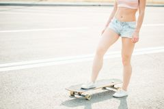 Close up of lady leg resting after extreme ride her wooden longboard skateboard royalty free stock photo