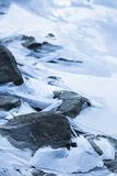Close up on lake bank rocks surrounded with frozen ice plaques on groundfloor. Close up on lake bank rocks surrounded with frozen ice plaques texture Stock Photo