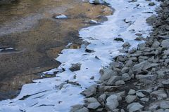 Close up on lake bank rocks surrounded with frozen ice plaques on groundfloor. Close up on lake bank rocks surrounded with frozen ice plaques texture Royalty Free Stock Photo