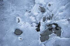 Close up on lake bank rocks surrounded with frozen ice plaques on groundfloor. Close up on lake bank rocks surrounded with frozen ice plaques texture Royalty Free Stock Images