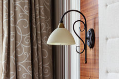 Close up of a lamp in a hotel room. Curtains background Stock Photo