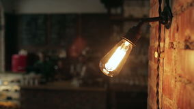 Close up of a lamp lights in a cafe. The staff behind the bar in the background